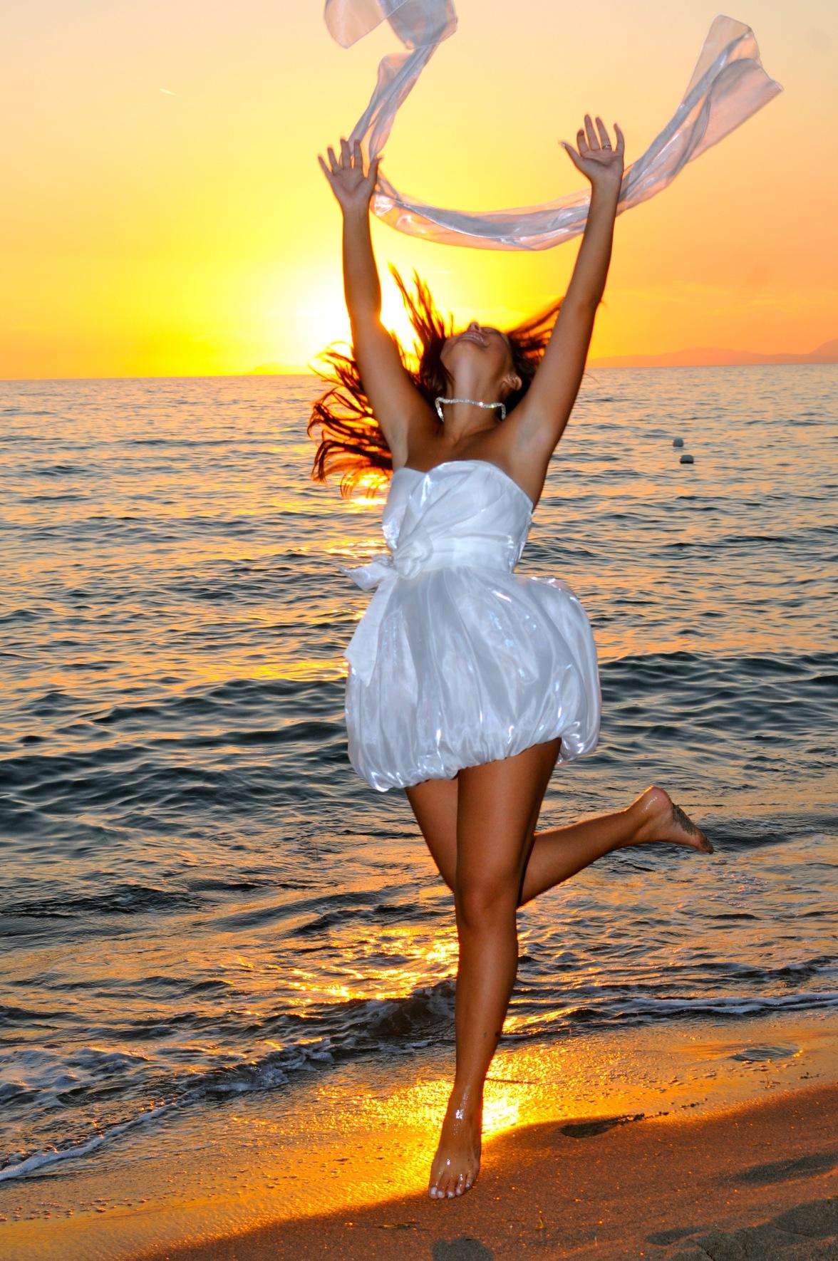giovane ragazza salta felice sulla spiaggia