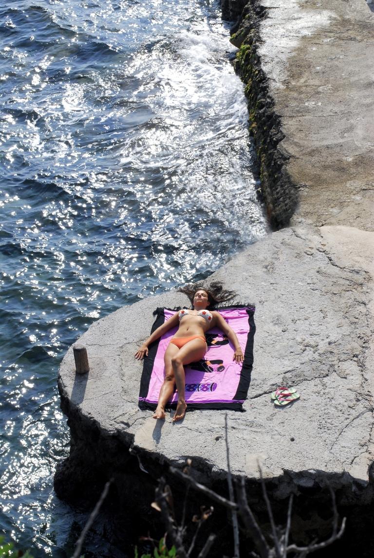 donna prende il sole su scoglio